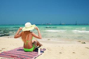 Rückansicht einer jungen asiatischen Frau, die Bikini und Sonnenhut trägt, um sich am Strand zu sonnen.