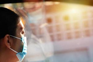 Frau, die eine Maske trägt, die sich allein und traurig fühlt, die in einem Auto während der Coronavirus-Krankheit sitzt foto