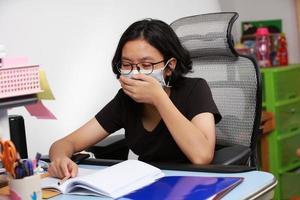 Mädchen mit einer Gesundheitsmaske, die niest, weil sie krank unter Quarantäne gestellt ist und zu Hause bleibt foto