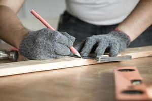 Zimmermann, der Holz mit Hintergrund des Kopierraums misst