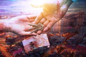 Hände, die Schlüssel mit Stadtüberlagerung übergeben foto