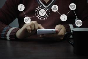 Mann mit Smartphone mit Symbolüberlagerung foto
