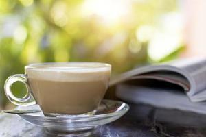 heißer Kaffee auf einem Tisch mit Buch foto