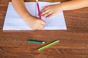 Kind schreibt in ein Notizbuch
