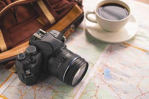 Kamera und Kaffee mit einer Tasche auf einer Karte foto