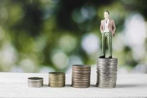 Geschäftsperson Figur, die auf Geldstapeln steht foto