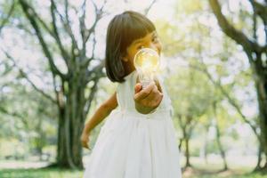 süßes junges Mädchen, das eine Glühbirne hält foto
