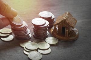 Münzen mit einem kleinen Modellhaus foto