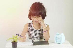 junges asiatisches Mädchen, das am Schreibtisch schreibt foto