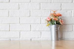 eine weiße Wand und eine dekorative Blume auf einem Holztisch
