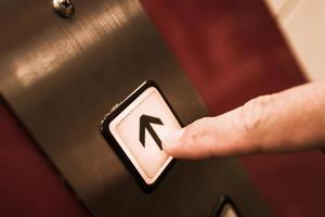 Finger, der einen Aufwärtsknopf in einem Aufzug drückt