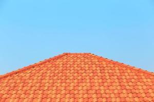 orangefarbene Ziegel auf einem Dach eines Hauses gegen einen Hintergrund des blauen Himmels
