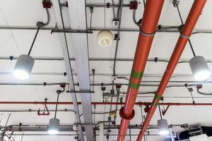 rote Pipeline, die Wasser in einem Industriegebäude löscht foto