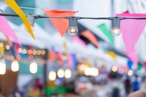 Glühbirnen und Partyflaggen für eine Geburtstagsgartenparty foto