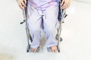Patientin in einem Rollstuhl, der in einem Krankenhauskorridor sitzt