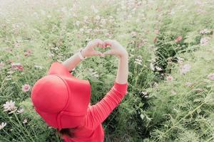 weibliche Hände des roten Hutes, die ein Herzsymbol im Blumenfeld bilden