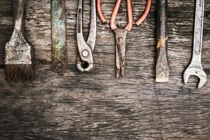 Mechanikerwerkzeuge auf schmutzigen hölzernen Hintergrund gesetzt