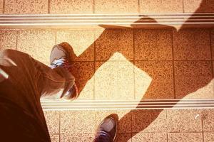 ein Schatten eines Mannes, der auf Steintreppen hinaufgeht