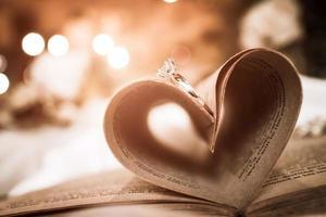 abstrakter Herzformschatten von zwei Eheringen auf einem Buch