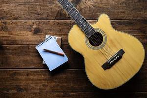 Draufsicht auf eine Gitarre und einen Notizblock foto