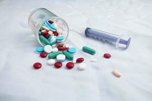 Pillen und eine Spritze auf weißem Hintergrund