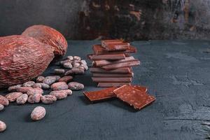 Schokolade und Kakaobohnen auf dunklem Hintergrund