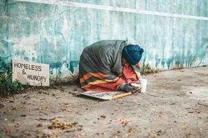 Bettler, die mit obdachlosen Nachrichten auf der Straße sitzen, helfen bitte foto