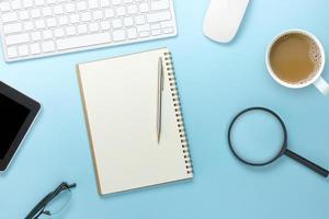 Draufsicht des leeren Notizbuchs mit Bürowerkzeug auf weichem blauem Hintergrund foto