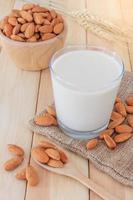 Mandelmilch mit Mandeln auf Holztisch foto