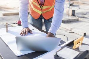 Ingenieur Planung auf Laptop mit Blaupausen foto