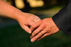 Jungvermählten Händchen haltend foto