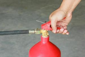 Hand den Abzug des Feuerlöschers drücken foto