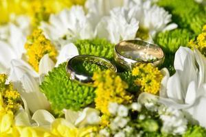 silberne Eheringe auf einem Blumenstrauß foto