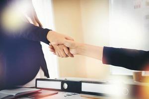 Geschäftsleute, die Hände schütteln, während sie am Arbeitsplatz sitzen foto