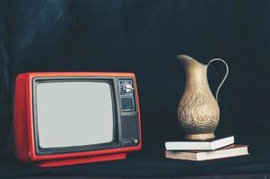 altes Retro-TV-Stillleben mit Blumenvase auf Büchern