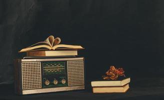 herzförmige Bücher auf Retro-Radioempfängern mit getrockneten Blumen foto