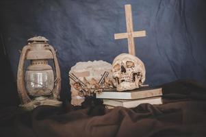 Stillleben mit Totenköpfen auf Büchern, alten Lampen, trockenen Blumen und gekreuzten Waffen foto