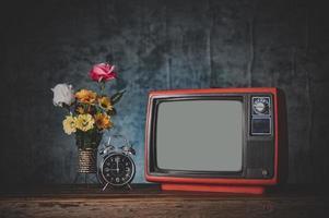 altes Retro-TV-Stillleben mit Uhr und Blumenvase