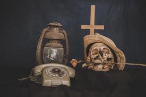 Stillleben im Retro-Stil mit einem Schädel und einer alten Lampe und einem Kreuz