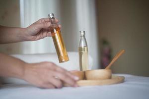 Hand hält eine Flasche ätherisches Öl und Spa-Behandlungen foto