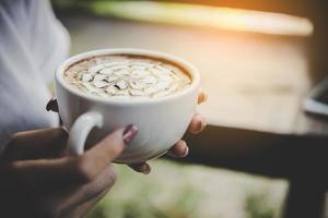 Frauenhand hält eine Tasse Kaffee