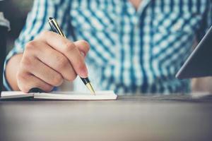 Nahaufnahme der Mannhandschrift im Notizbuch mit Stift foto
