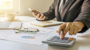Asiatische Buchhalter verwenden Taschenrechner, um Unternehmensbudgets, Finanzideen und Finanzbuchhaltung zu berechnen