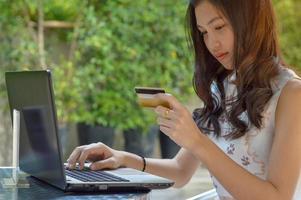 asiatisches Mädchen, das Kreditkarte hält und Laptop verwendet