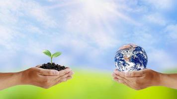 Austausch von Planeten in den Händen des Menschen mit jungen Pflanzen in den Händen des Menschen, das Konzept des Tages der Erde und die Erhaltung der Umwelt. Elemente dieses Bildes von der NASA dekoriert foto