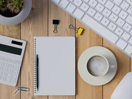 Draufsicht auf Schreibtischarbeitsplatz mit leerem Notizbuch foto