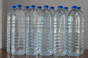 Reihen von Plastikwasserflaschen auf dem Tisch foto