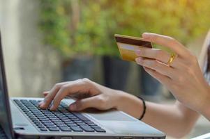 junges Mädchen, das Kreditkarte hält und Laptop verwendet