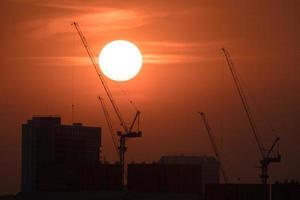 Kräne und Gebäude bei Sonnenuntergang silhouettiert