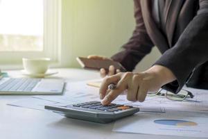 Geschäftsleute verwenden einen Taschenrechner, um ihre Finanzinformationen, Arbeitsideen und Teamwork-Strategien zu überprüfen foto